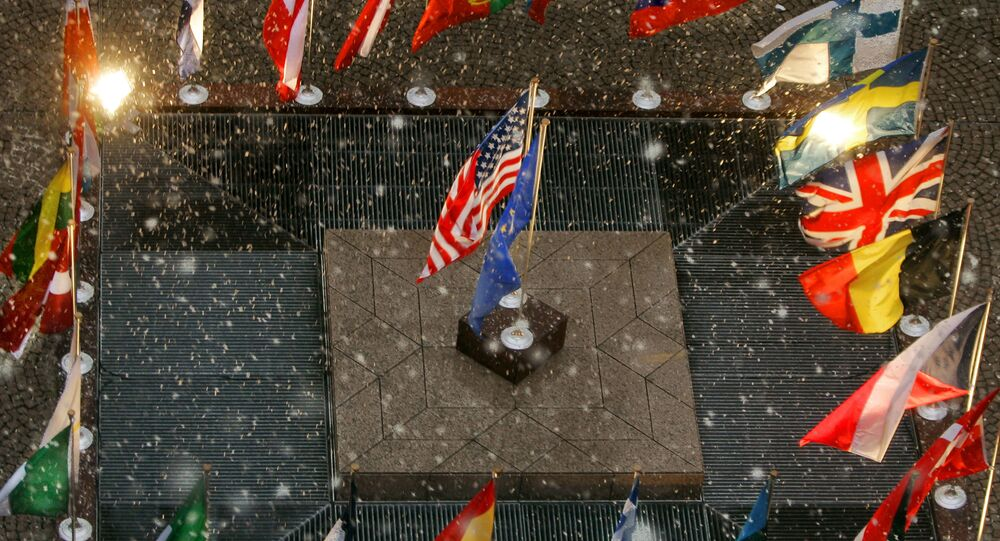 The flags of the United States and the European Union stand amid the national flags of the European Union nations during a gentle snowfall at European Union headquarters  in Brussels, Belgium, Tuesday, Feb. 22, 2005