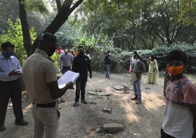 A Delhi police volunteer hands out COVID-19 test results in New Delhi, India, Friday, Nov. 6, 2020