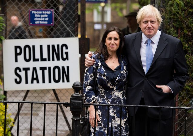 London Mayor Boris Johnson (R) stands with his wife Marina Wheeler (L) after casting his vote in the local elections