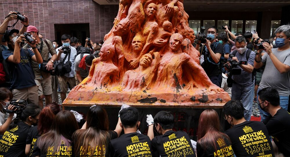 University students clean the Pillar of Shame statue at the University of Hong Kong on the 32nd anniversary of the crackdown on pro-democracy demonstrators at Beijing's Tiananmen Square in 1989, in Hong Kong, China June 4, 2021