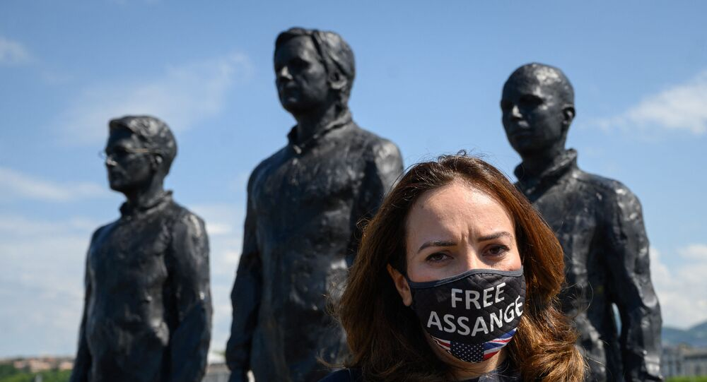 English lawyer and partner of Wikileaks founder Julian Assange, Stella Morris wearing a facemask reading: Free Assange poses next to statues representing  Edward Snowden, Julian Assange and Chelsea Manning during the Geneva Appeal for the immediate release of Wikileaks founder Julian Assange in Geneva, on June 4, 2021. - The Geneva Appeal was launched at a virtual event attended by the partner of the founder of WiikiLeaks, and the mayor of Geneva as well as several personalities, including the United Nations Special Rapporteur on Torture.