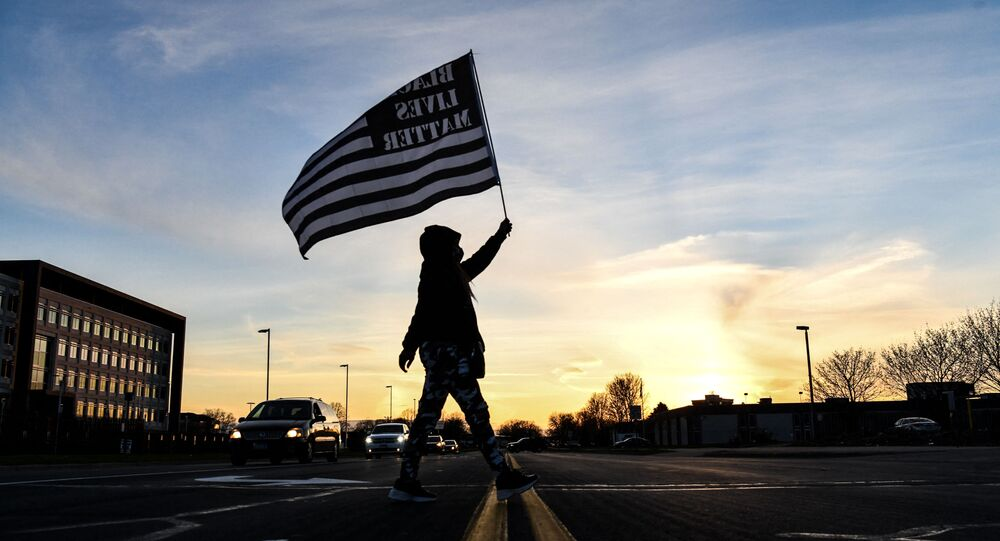 A demonstrator marches, holding a Black Lives Matter flag, during the sixth night of protests over the shooting death of Daunte Wright by a police officer in Brooklyn Center, Minnesota on April 16, 2021