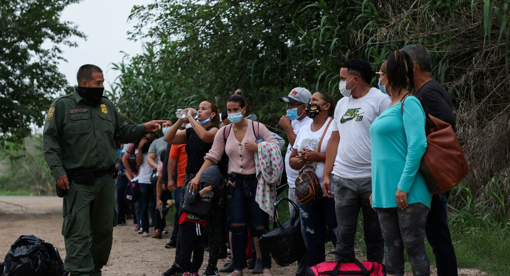 Migrants from Venezuela await transportation to a U.S. border patrol facility after crossing the Rio Grande river into the United States from Mexico in Del Rio, Texas, U.S., May 11, 2021