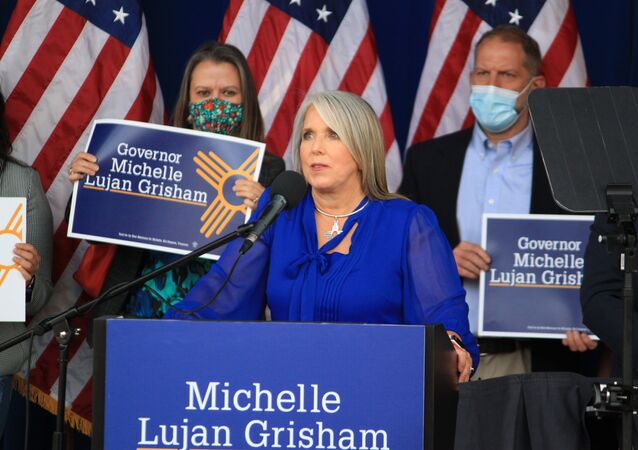New Mexico Gov. Michelle Lujan Grisham looks up toward a group of protesters as she announces her intention to seek reelection during a campaign rally in Albuquerque, New Mexico, on Thursday, June 3, 2021. The rally was cut short as the protesters' chants drowned out Lujan Grisham and the other speakers. (AP Photo/Susan Montoya Bryan)