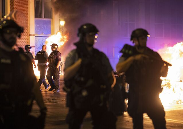 Police stand guard after protesters set fire to dumpsters after a vigil was held for Winston Boogie Smith Jr. early on Saturday, June 5, 2021.