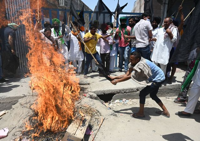 Farmers holding black flags shout slogans as they burn an effigy of Prime Minister Narendra Modi while they observe a 'Black Day' marking six months of continued protest against the central government's agricultural reforms, at the Delhi-Haryana state border in Kundli on May 26, 2021.