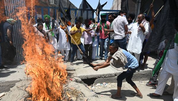 Farmers holding black flags shout slogans as they burn an effigy of Prime Minister Narendra Modi while they observe a 'Black Day' marking six months of continued protest against the central government's agricultural reforms, at the Delhi-Haryana state border in Kundli on May 26, 2021.  - Sputnik International