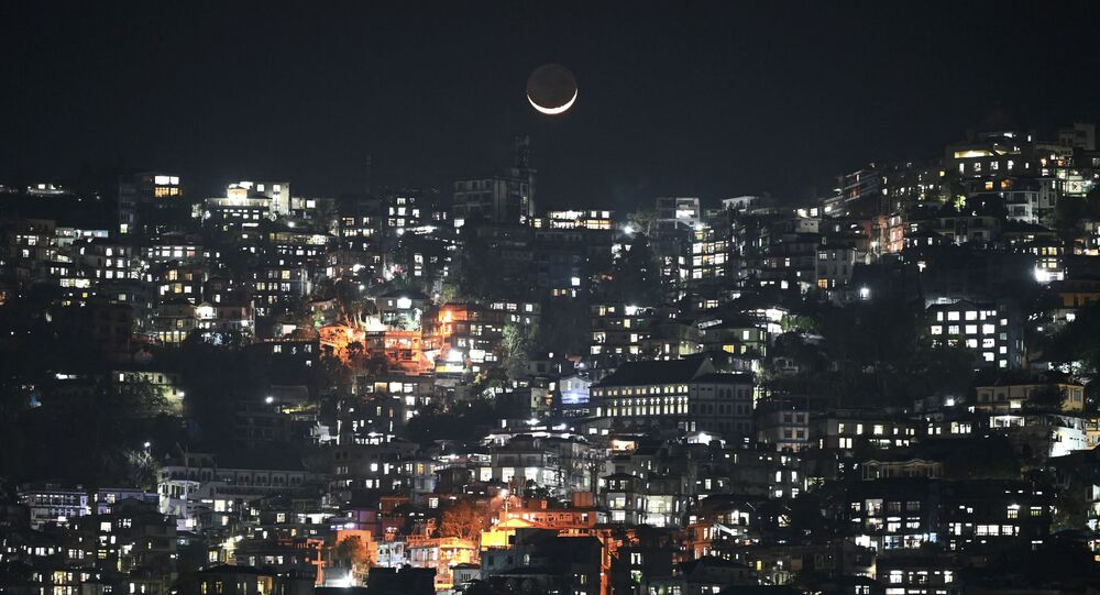A general view shows a crescent moon over homes on a hillside in Aizawl, the capital of the northeastern Indian state of Mizoram on March 16, 2021
