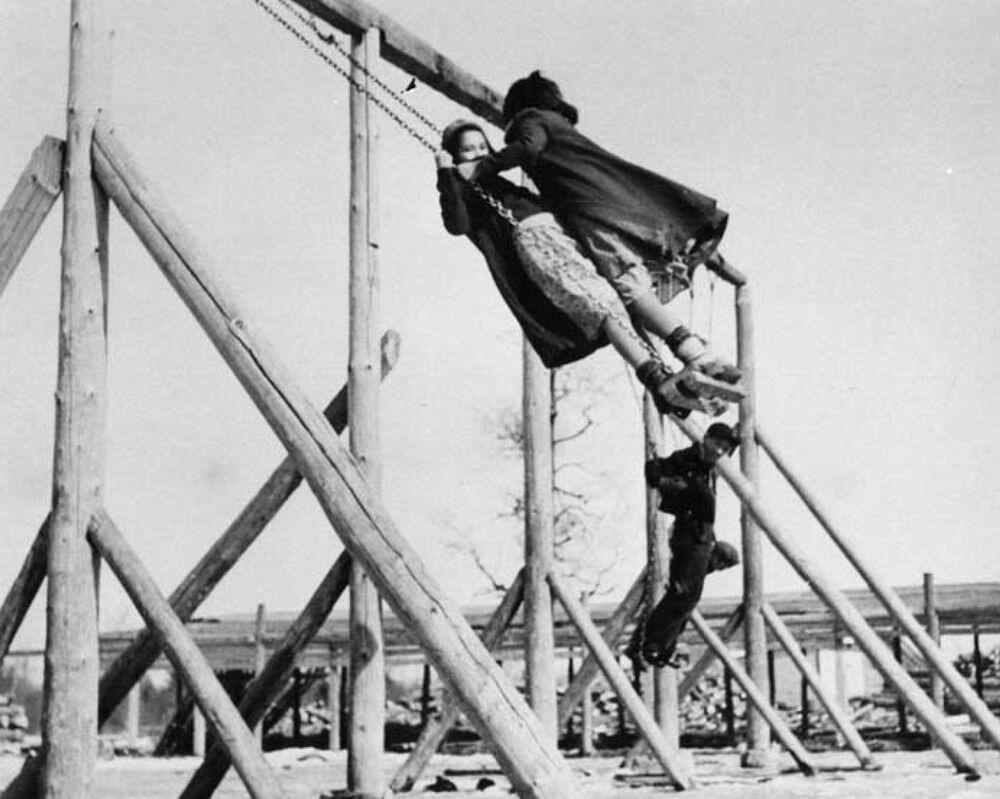 Children play on swings at the Bishop Horden Memorial School, a residential school in the indigenous Cree community of Moose Factory, Ontario, Canada circa 1940s.