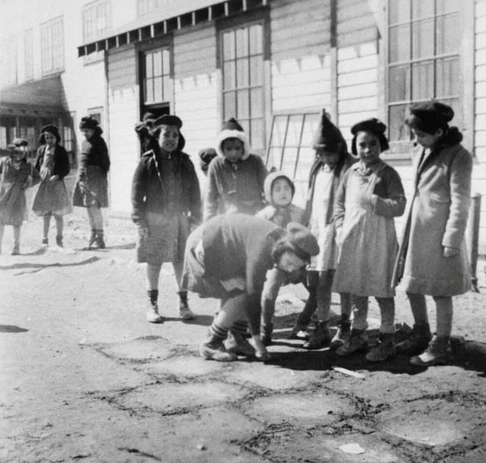 Girls play hopscotch outside the Bishop Horden Memorial School, a residential school in the indigenous Cree community of Moose Factory, Ontario, Canada in 1947.