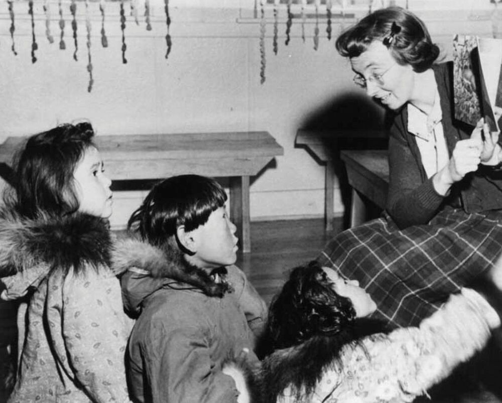 A teacher reads to students at a residential school in Aklavik, Northwest Territories, Canada circa 1950.