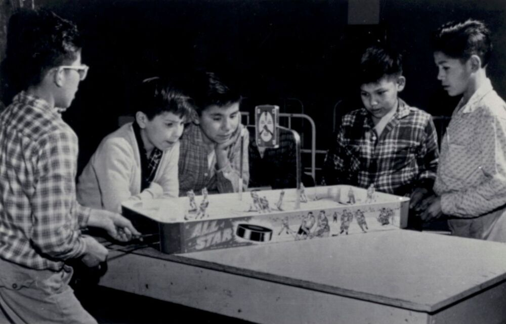 Boys play table hockey at the Shingwauk Indian Residential School in Sault Ste. Marie, Ontario, Canada circa 1960s.
