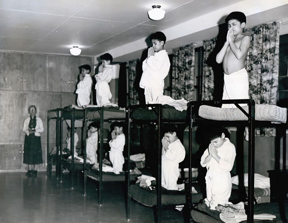 Boys pray on bunk beds in a dormitory at the Bishop Horden Memorial School, a residential school in the indigenous Cree community of Moose Factory, Ontario, Canada in 1950.