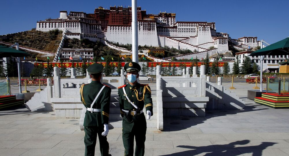 FILE PHOTO: Paramilitary police officers swap positions during a change of guard in front of Potala Palace in Lhasa, during a government-organised tour to Tibet Autonomous Region, China, 15 October 2020. REUTERS/Thomas Peter/File Photo