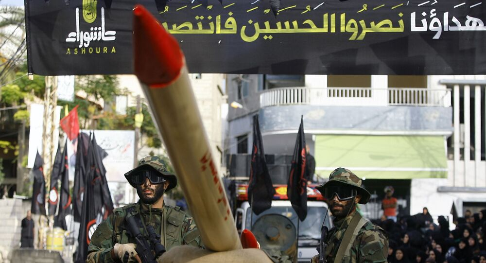 In this Sunday, Oct. 9, 2016 photo, Hezbollah fighters stand atop a car mounted with a mock rocket, as they parade during a rally to mark the seventh day of Ashoura, in the southern village of Seksakiyeh, Lebanon.