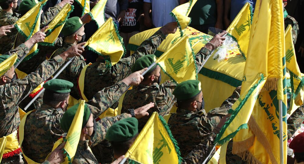 Hezbollah fighters raise their group flags, as they salut the coffin of their comrade Mohammed Tahhan who was shot dead on Friday by Israeli forces along the Lebanon-Israel border, during his funeral procession, in the southern village of Adloun, Lebanon, Saturday, May 15, 2021