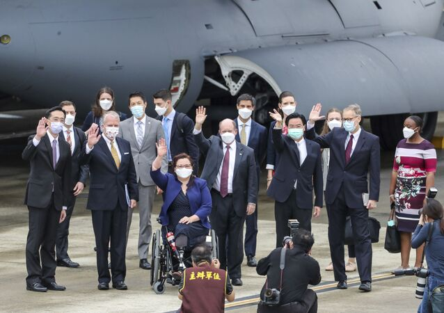 Taiwan's Foreign Minister Joseph Wu, fourth from right, waves with U.S. senators to his right Democratic Sen. Christopher Coons of Delaware, a member of the Foreign Relations Committee, Democratic Sen. Tammy Duckworth of Illinois and Republican Sen. Dan Sullivan of Alaska, members of the Armed Services Committee on their arrival at the Songshan Airport in Taipei, Taiwan on Sunday, June 6, 2021