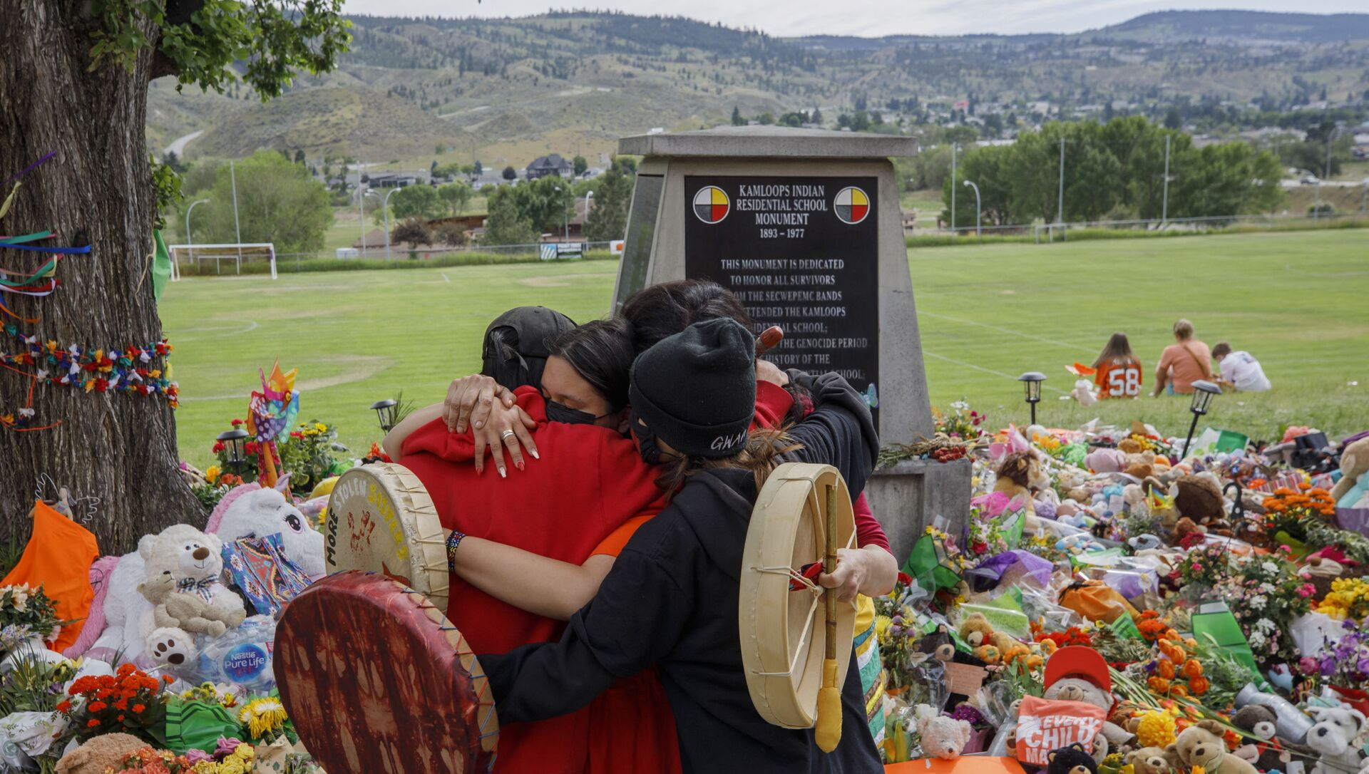 Members of the Mosakahiken Cree Nation hug in front of a makeshift memorial at the former Kamloops Indian Residential School to honour the 215 children whose remains have been discovered buried near the facility. - Sputnik International, 1920, 29.07.2021