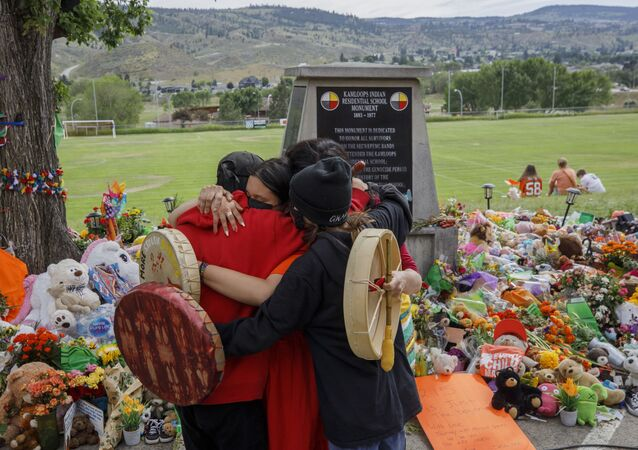 People from Mosakahiken Cree Nation hug in front of a makeshift memorial at the former Kamloops Indian Residential School to honour the 215 children whose remains have been discovered buried near the facility,