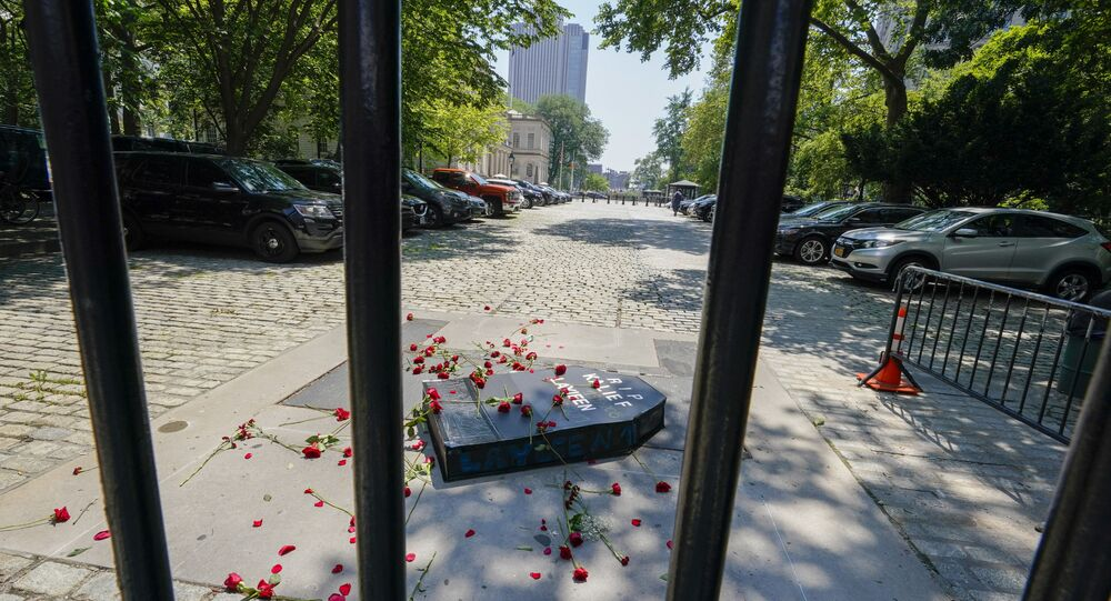 A cardboard coffin and red flowers are seen inside City Hall after activist threw them over the gate during a march and rally to demand the end of solitary confinement in New York, Monday, June 7, 2021.