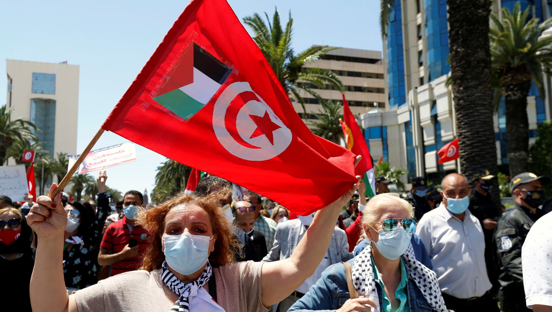 A demonstrator holds a Tunisia flag with a Palestinian flag attached during a protest to express solidarity with the Palestinian people, in Tunis, Tunisia, May 19, 2021. - Sputnik International, 1920, 08.06.2021