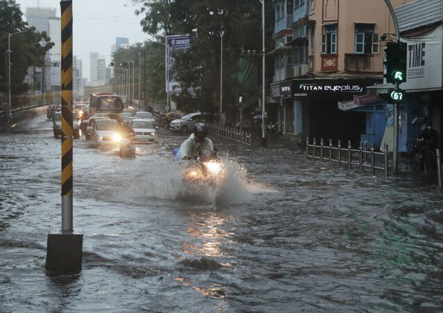 Commuters wade through a waterlogged street during a heavy rain in Mumbai, India, Monday, May 17, 2021