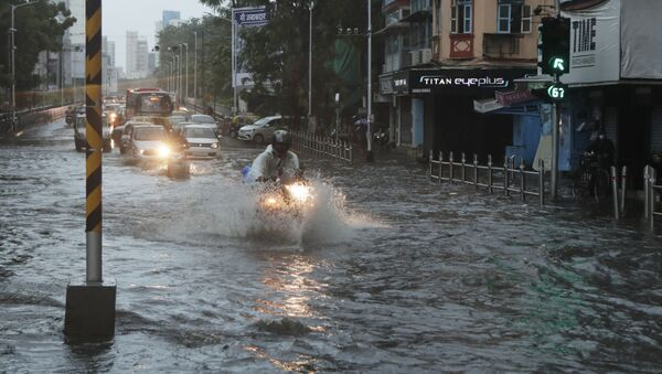 Commuters wade through a waterlogged street during a heavy rain in Mumbai, India, Monday, 17 May 2021 - Sputnik International
