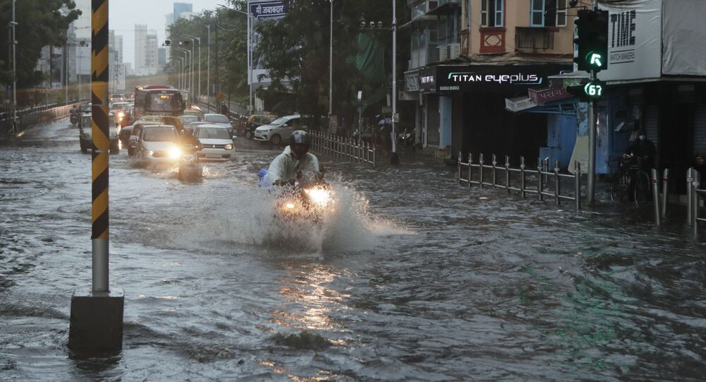 Commuters wade through a waterlogged street during a heavy rain in Mumbai, India, Monday, 17 May 2021