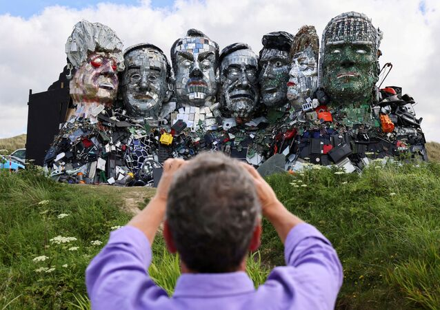 A man photographs Mount Recyclemore, an artwork depicting the G7 leaders looking towards Carbis Bay, made from electronic waste by Joe Rush and Alex Wreckage, ahead of the G7 summit, at Hayle Towans in Cornwall, Britain, 8 June 2021.