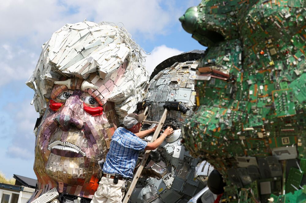 A man makes an adjustment to Mount Recyclemore, an artwork depicting the G7 leaders looking towards Carbis Bay in Cornwall, made from electronic waste by Joe Rush and Alex Wreckage.