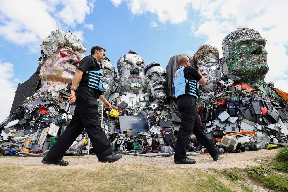 Police liaison officers walk by 'Mount Recyclemore', an artwork depicting the G7 leaders.