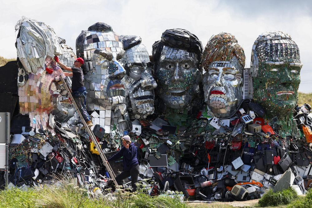 Alex Wreckage makes an adjustment to 'Mount Recyclemore', an artwork depicting the G7 leaders looking towards Carbis Bay in Cornwall, made from electronic waste by him and Joe Rush, ahead of the G7 summit.