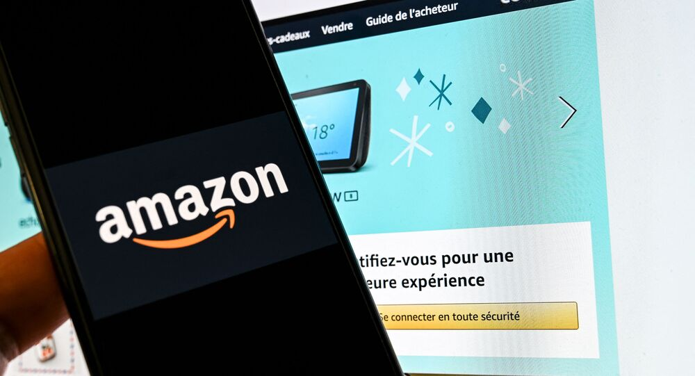 In this photograph taken on November 18, 2020 in Lille, a person poses with a smartphone showing an Amazon logo, in front of a computer screen displaying the home page of Amazon France sales website.