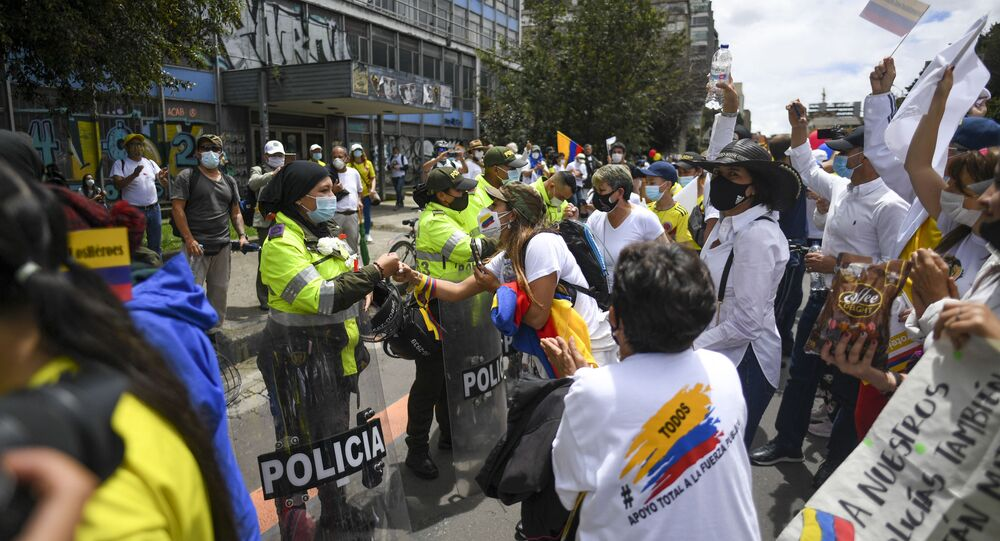 People greet police officers during a demonstration to oppose road blockades and violence, after a month of national protests, in Bogota, on 30 May 2021.