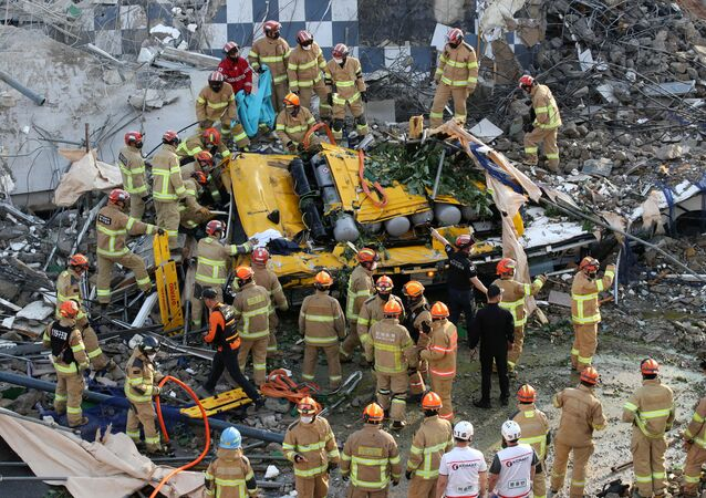 South Korean firefighters search for passengers from a bus trapped by the debris of a collapsed building in Gwangju, South Korea, June 9, 2021.