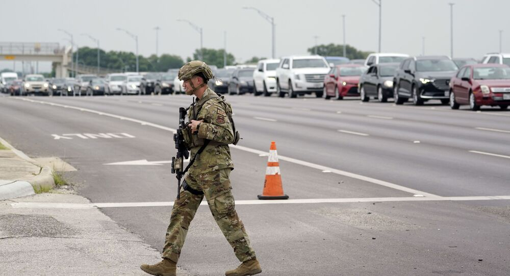 A military policeman walks past traffic outside of a JBSA-Lackland Air Force Base gate, Wednesday, June 9, 2021, in San Antonio. The Air Force was put on lockdown as police and military officials say they searched for two people suspected of shooting into the base from outside.