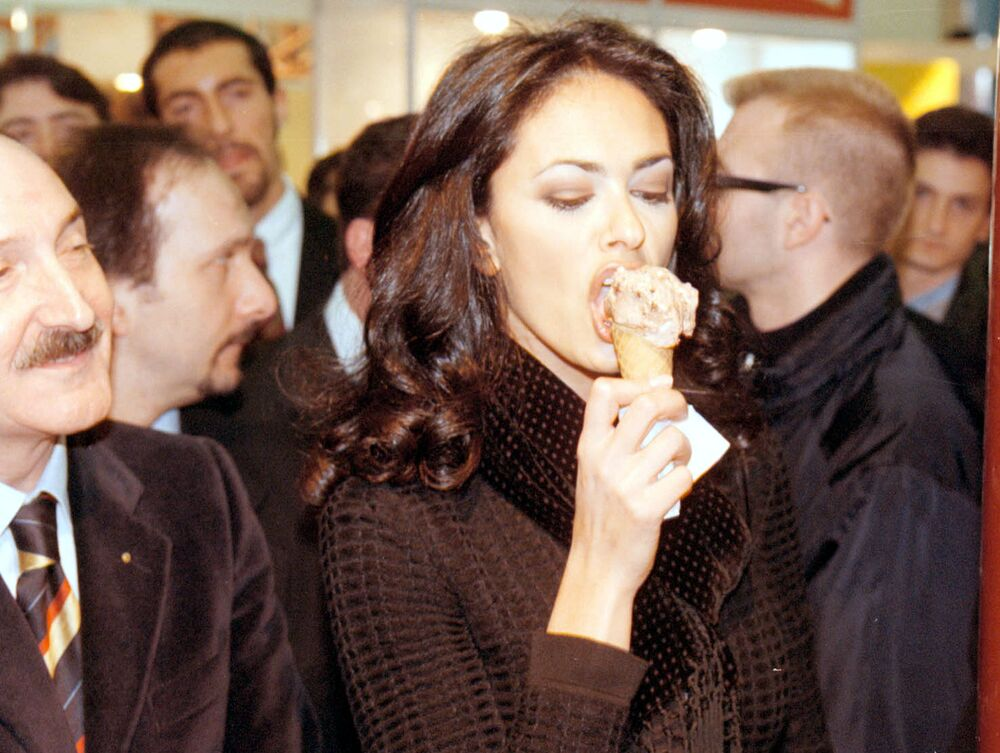 Italian actress Maria Grazia Cucinotta tastes some ice cream, as curious bystanders look on, during her visit to the Ice Cream Trade Fair in Rimini, central Italy, on 24 January 1998.