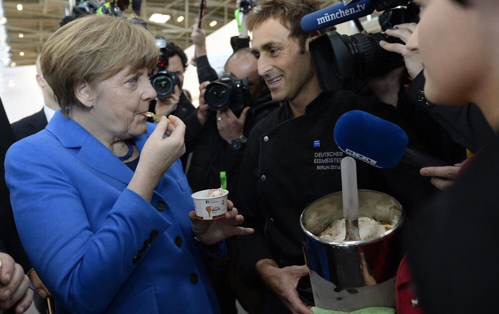 German Chancellor Angela Merkel tastes ice cream she was given by German Gelato Champion 2014, Adriano Colle, (C) as she visited the International Handwerksmesse trade fair in Munich, Germany, on 13 March 2015.