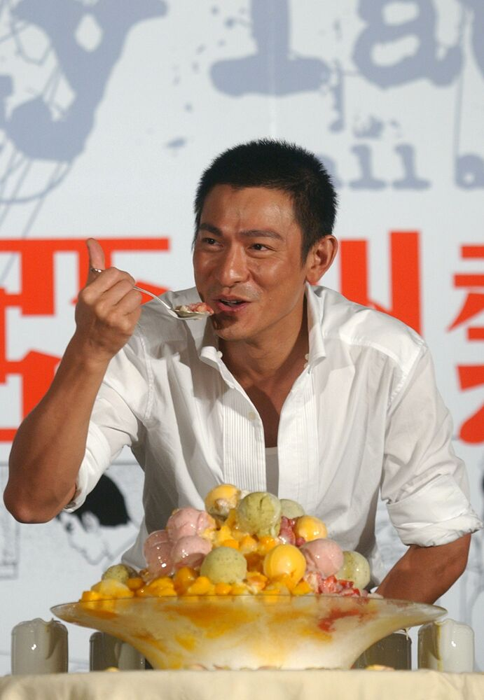 Hong Kong singer and actor Andy Lau tastes ice cream during a photocall on 23 August 2005, in Taipei, Taiwan.