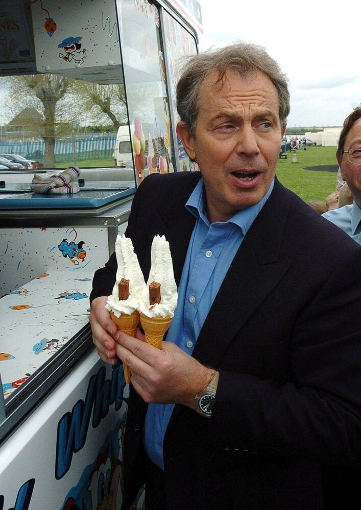 Then-British Prime Minister Tony Blair buys two ice cream cones for himself and Chancellor Gordon Brown (not shown) during a visit to the strand park in Gillingham, Kent, 2 May 2005.