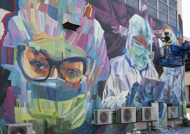 A worker gives final touches to a graffiti that tributes to Malaysian workers on the frontline against the COVID-19 pandemic outside a hospital in Kuala Lumpur, Malaysia, Friday, Jan. 29, 2021
