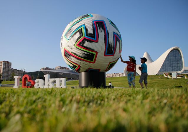Children play next to the giant model of the official UEFA Euro 2020 match ball in Baku, Azerbaijan, 3 June 2021.