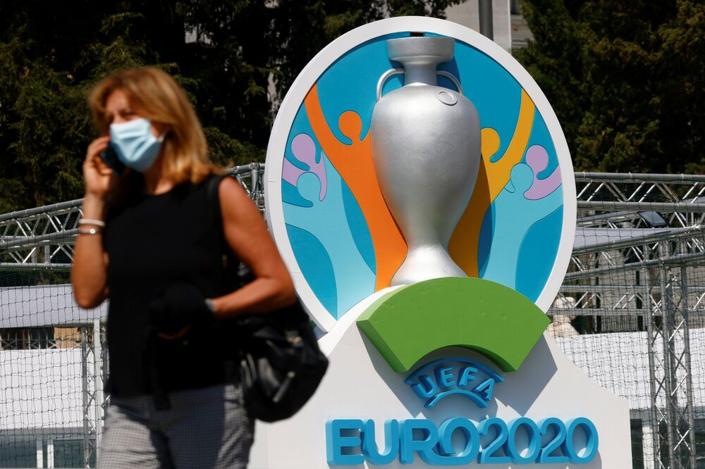 A woman wearing a protective mask walks past the logo of UEFA Euro 2020 at the fan zone at Piazza del Popolo in Rome.