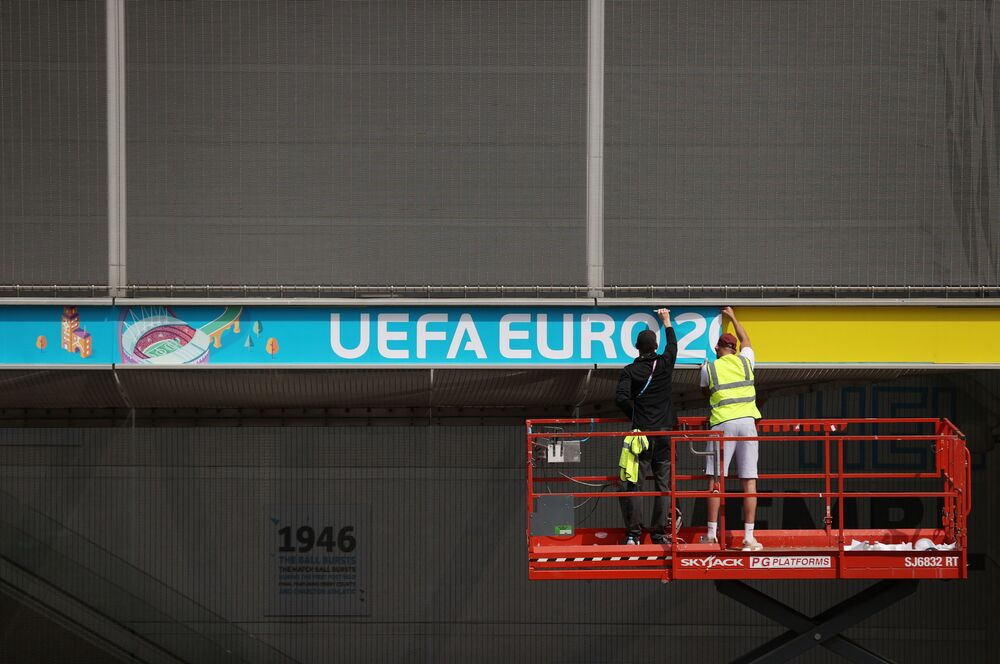 Workers attach Euro 2020 signage to Wembley Stadium in London.