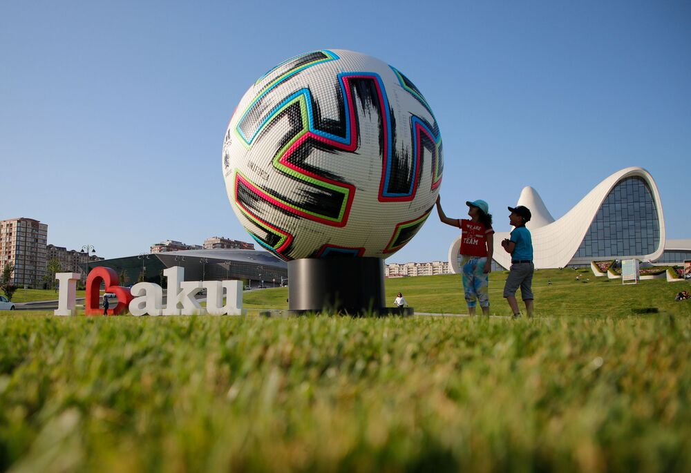 Children play next to the giant model of the official UEFA Euro 2020 match ball in Baku, Azerbaijan.