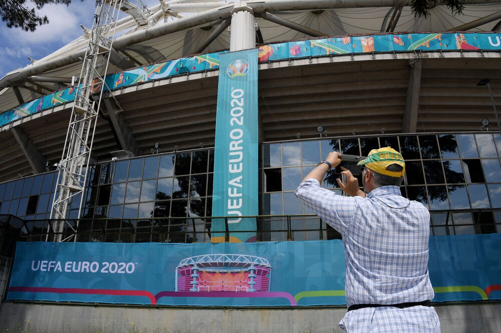 Rome's Stadio Olimpico prepares for opening match, 9 June 2021. A man takes a picture of the outside of the stadium ahead of the tournament.