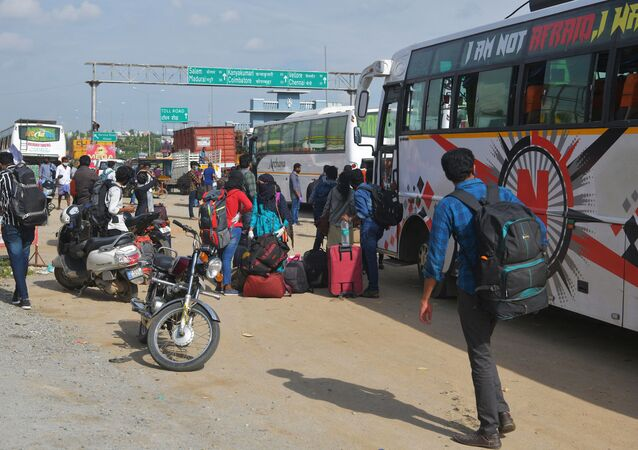 People wait on the outskirts of Bangalore to board buses and return to their home towns on the border of the states of Karnataka and Tamil Nadu, as another lockdown looms to tackle the surge in COVID-19 coronavirus cases on 13 July 2020.