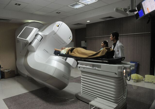 Radiation technologist, Yogesh Ninave (R),  and coordinator, Khyati Panchal (L), observe a cancer patient lying in India's first Truebeam Radiotherapy Technology Linear Accelerator at the Healthcare Global hospital in Ahmedabad, in Gujarat state, on 13 December 2011.