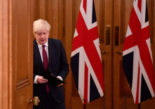 Britain's Prime Minister Boris Johnson walks past union flags as he arrives to attend a virtual press conference inside 10 Downing Street in central London on December 19, 2020.