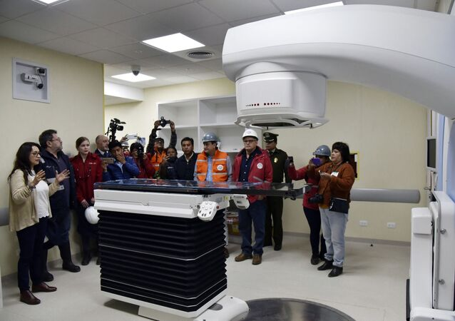 The director of Nuclear Technology, Dr Vivian Rada (L) shows a medical linear accelerator (LINAC) -used for cancer treatments- to Bolivian government authorities during a visit to the Investigation Centre of Nuclear Medicine, in El Alto, Bolivia, on March 10, 2020. - Russian company Rosatom is building the first nuclear research center for medical and agricultural purposes in the Bolivian city of El Alto, which costs 351 million dollars
